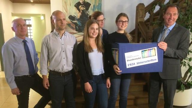 Fünf Leute übergeben eine Schachtel mit Unterschriftenbögen an Landschreiber Peter Vetter