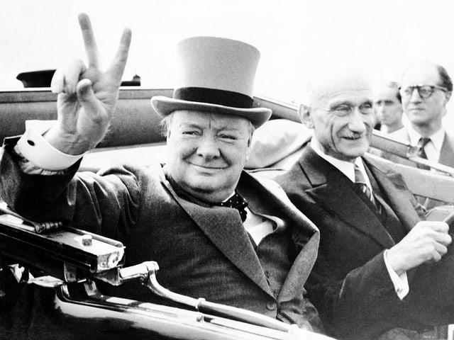 Winston Churchill (linke Seite) mit Zylinder in Auto sitzend, Victory-Zeichen machend. Neben ihm sitzt Robert Schuman