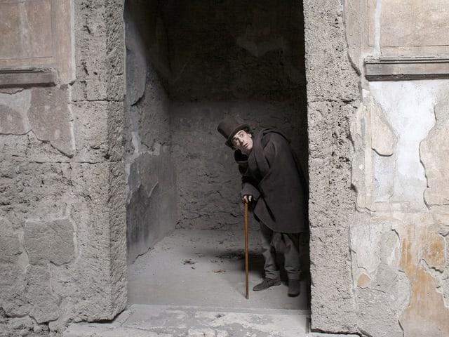 Ein Mann mit Hut und Stock schaut zwischen zwei Steinmauern hervor.