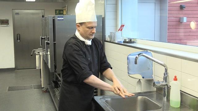 Ein Koch wäscht sich die Hände.