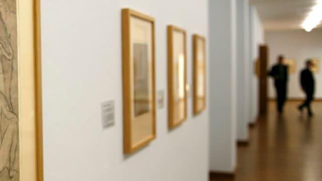 Bilder hängen in einem Museum an der Wand