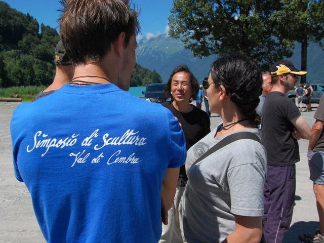 Drei Teilnehmer des Holzbildhauer-Symposiums Brienz begrüssen sich.