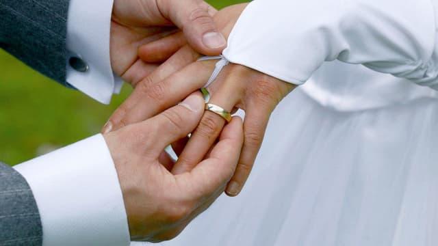 Männerhand steckt Frauenhand Ring an den Finger.