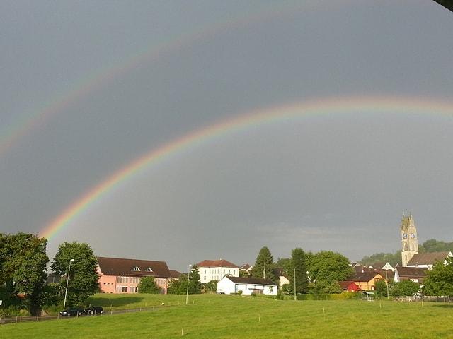 Regenbogen am Abendhimmel über Andelfingen. Darunter das Dorf mit der Kirche.