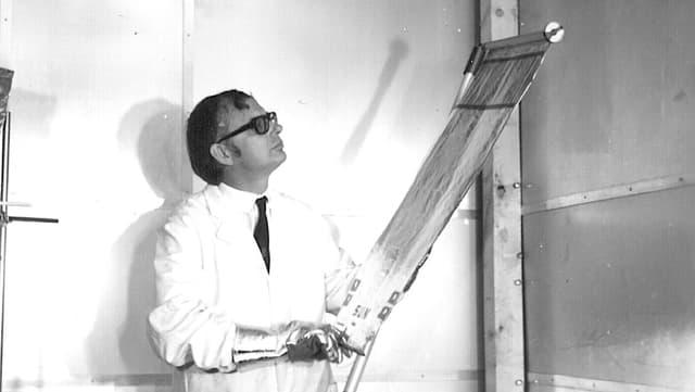 Schwarzweissfoto: Mann in weissem Laborkittel zieht ein silbern glänzendes Rollo auf.