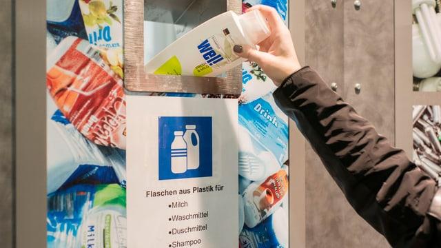 Frau wirft Plastikflasche in Entsorgungsstelle.