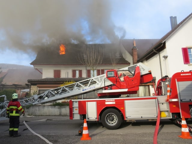 Drehleiter der Feuerwehr steht vor dem brennenden Haus