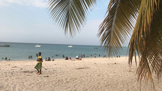Schöner Sandstrand mit Menschen und Palmen.