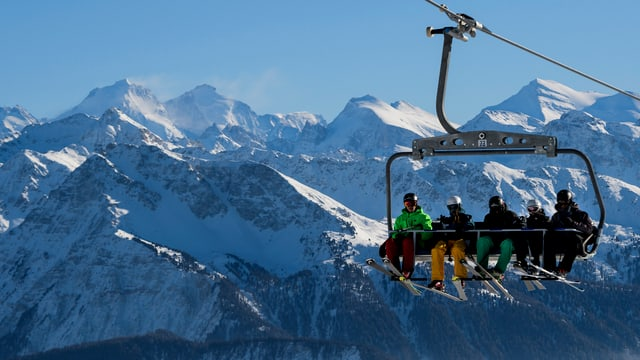 Skifahrer auf einem Sessellift, im Hintergrund verschneite Berghänge.