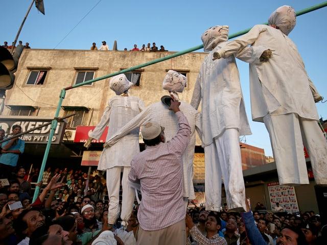Demonstranten mit erhängten Puppen, die die Vergewaltiger darstellen sollen