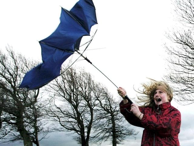 Der Wind reisst den Schirm aus der Hand eines Mädchens.