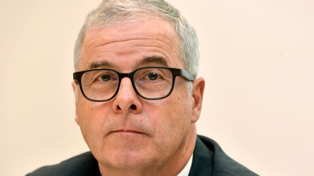 Ein Mann mit grauen Haaren und schwarzer Brille blickt in die Kamera.