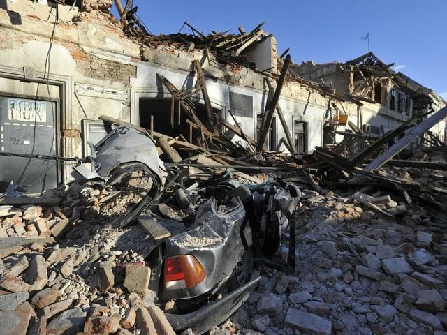 Schuttmassen haben ein Auto unter sich begraben, dahinter eine sehr stark beschädigte Häuserzeile.