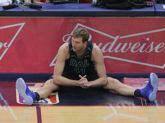 Dirk Nowitzki sitzt mit gespreizten Beinen auf dem Boden.