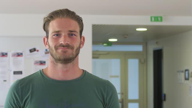 Ein Mann steht links im Bild im grünen T-Shirt. Im Hintergrund ist rechts eine Türe zu sehen und links eine Pinnwand.