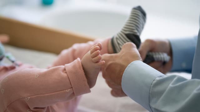 Männerhände halten Kinderfüsse