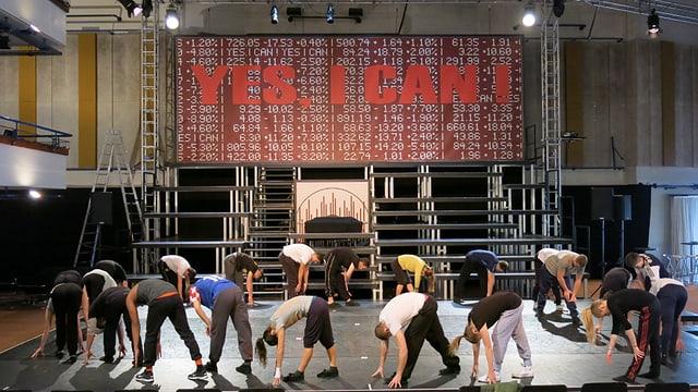 """Tänzerinnen und Tänzer auf einer grossen Bühne, alle bücken sich nach vorne. Auf einem grossen Bildschirm über ihnen steht """"yes, I can"""""""