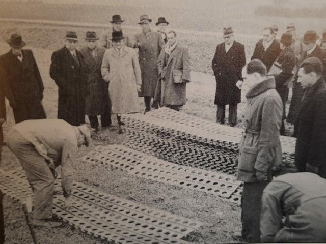 Auf einem historischen Bild stapeln Arbeiter Blechplatten.