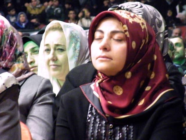 Zwei Frauen in einer Menschenmenge hören konzentriert und bewegt zu.