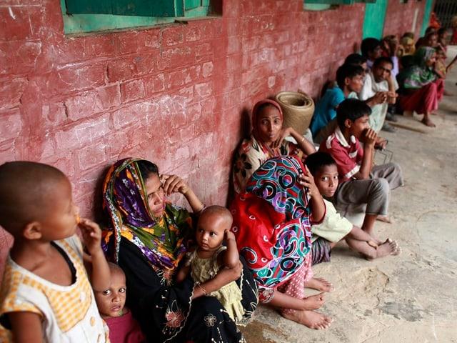 Frauen und Kinder sitzen vor einer Schule