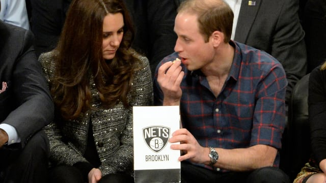 Kate und William sitzend. William hat eine Tüte Popcorn in der Hand.
