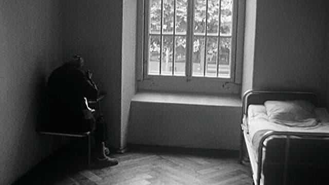 Schwarz-weiss-Bild eines Klink-Zimmers. Eine Frau sitzt in der Ecke an einem Tischchen.