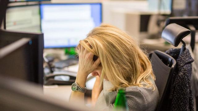 Börsenhändlerin vor Bildschirmen stützt ihren Kopf.