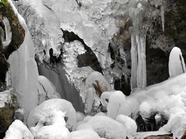 Ein Bach ist zugefroren und hat die Landschaft verzaubert.
