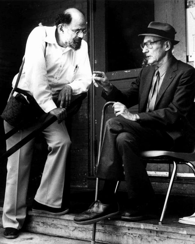 Allen Ginsberg steht und redet mit Burroughs, der auf einem Stuhl sitzt.