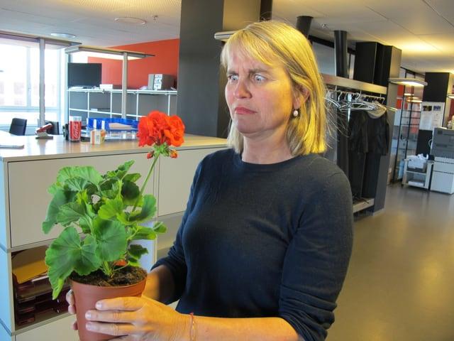 Produzentin Christine Hubacher hält ein Geranium in der Hand.