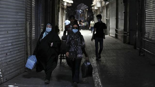 Personen mit Schutzmaske gehen an geschlossenen Geschäften vorbei.