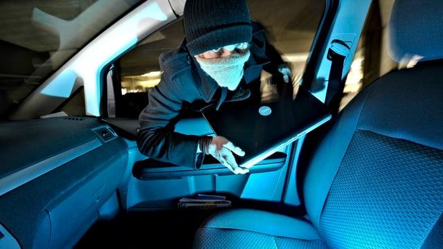 Ein junger Mann bricht in ein Auto ein und entwendet einen Laptop.