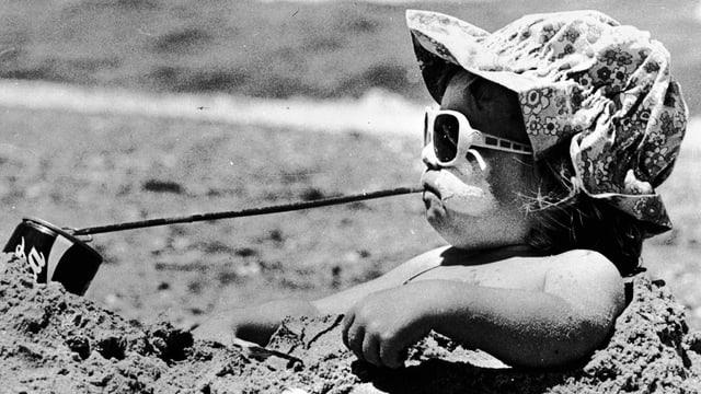Ein kleines Mädchen mit Sonnenbrille im Sand verbuddelt trinkt Cola mit einem sehr langen Strohhalm.