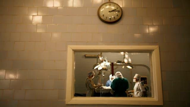 Tras ina fanestra ves'ins medis e gidanters ch'èn gist vi da ina operaziun