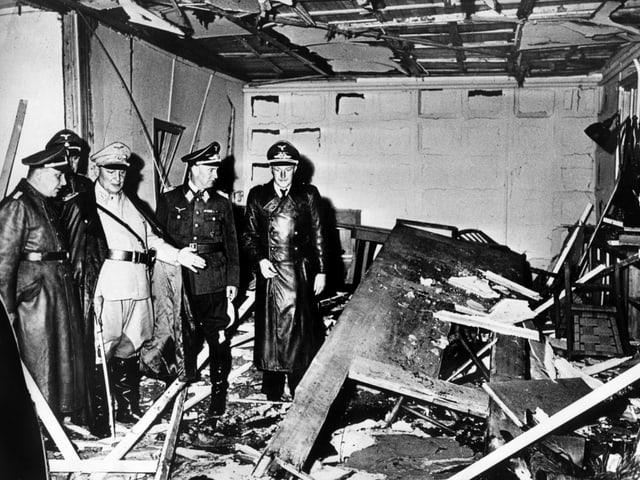 Historisches Schwarzweissfoto: Fünf Männer in Militäruniformen stehen in einem zerstörten Raum