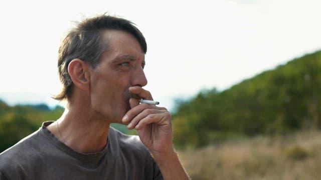 Ein Mann zieht an einer Zigarette.