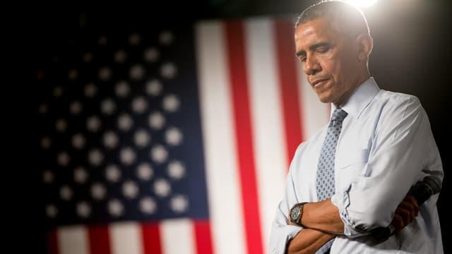 Obama steht mit verschränkten Armen und nachdenklichem Blick nach unten seitwärts vor einer US-Flagge, die im Hintergrund aufgehähngt ist.
