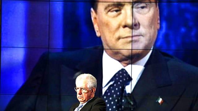 Mario Monti sitzt in einem TV-Studio. In seinem Rücken prangt das Konterfei Berlusconi in Übergrösse.