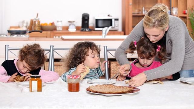 Drei kleine Kinder beim Essen, betreut von einer jungen Frau.