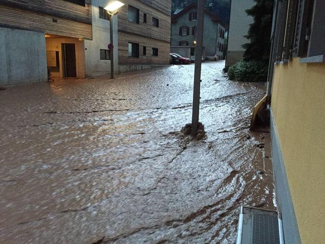 Überflutete Strasse, einige Häuser und Pfosten.
