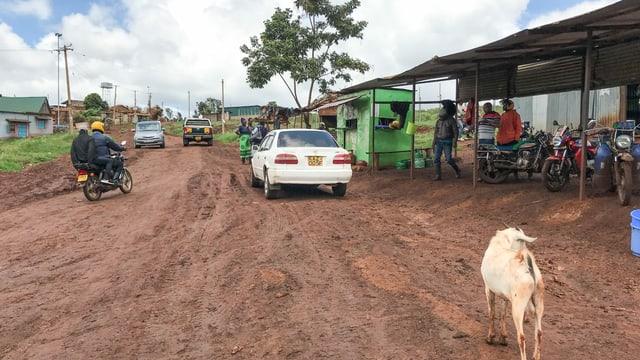 rote Sandstrasse mit Motorradfahrern, Autos und Ziege