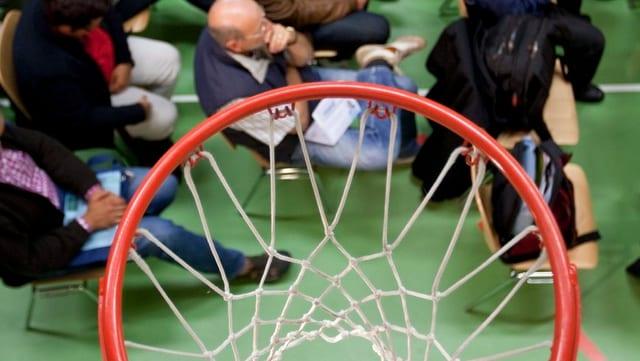 Blick durch einen Basketballkorb auf eine Versammlung.