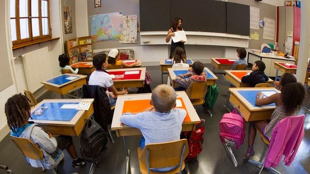 Kinder sitzen in einem Klassenzimmer und schauen zur Lehrerin vor der Wandtafel.