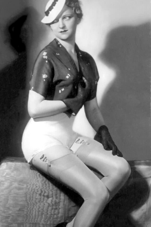 Ein Model posiert in Seidenstrümpfen und Strumpfhalter.