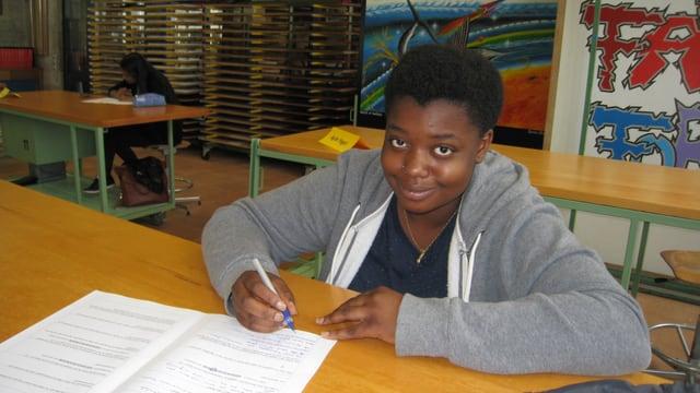 Die junge Frau sitzt an einem Werktisch und füllt einen Fragebogen aus