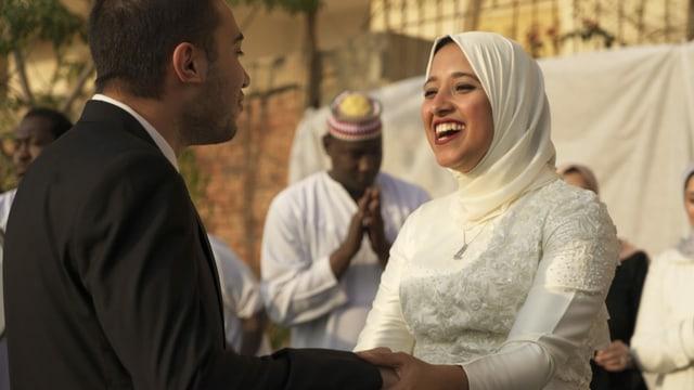 eine verhüllte Frau lächelt und hält einen Mann
