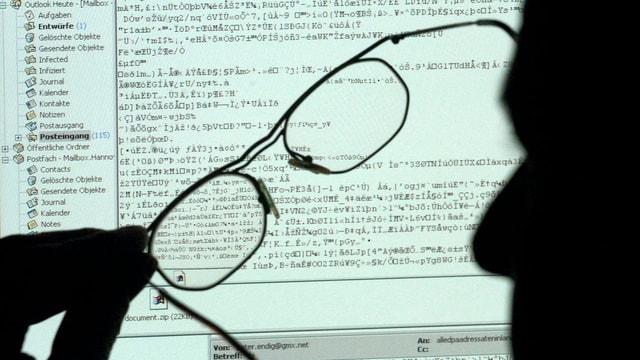 Schatten eines Mannes und einer Brille vor einem Computerbildschirm. Darauf wirre Symbole.