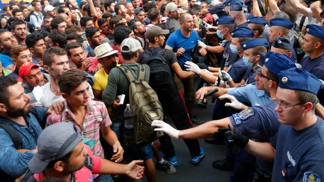 La polizia ungarais a la staziun en l'ost da Budapest vi da manar davant ils fugitivs.
