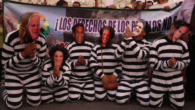 Demonstranten mit Masken und Häftlingskleidung.