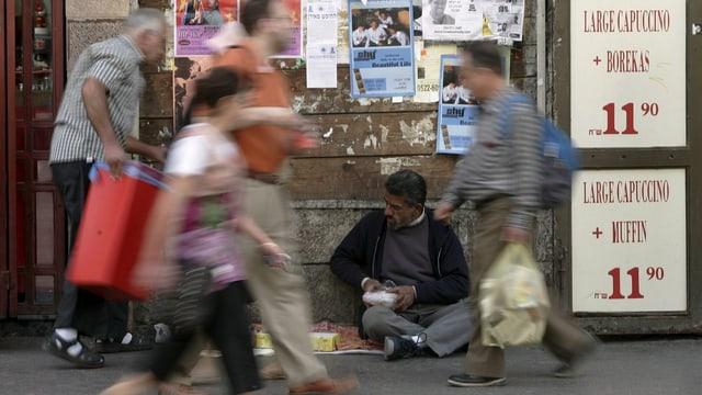 Menschen auf der Jaffastrasse gehen durchs Bild (verwischt), ein Bettler sitzt am Boden.